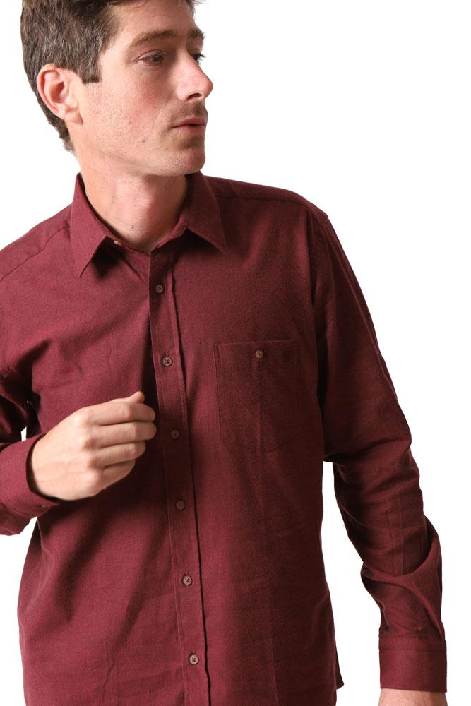 man looks to the side, about to adjust a button on the front of burgundy men's dress shirt