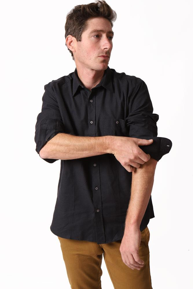 man adjusts cuff on black long sleeve woven shirt