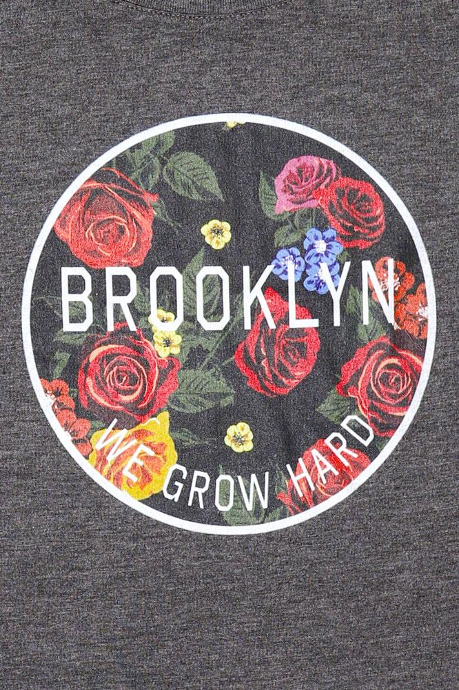detail of charcoal off shoulder shirt with circle of flowers on front with text of we grow hard, and Brooklyn intersecting it