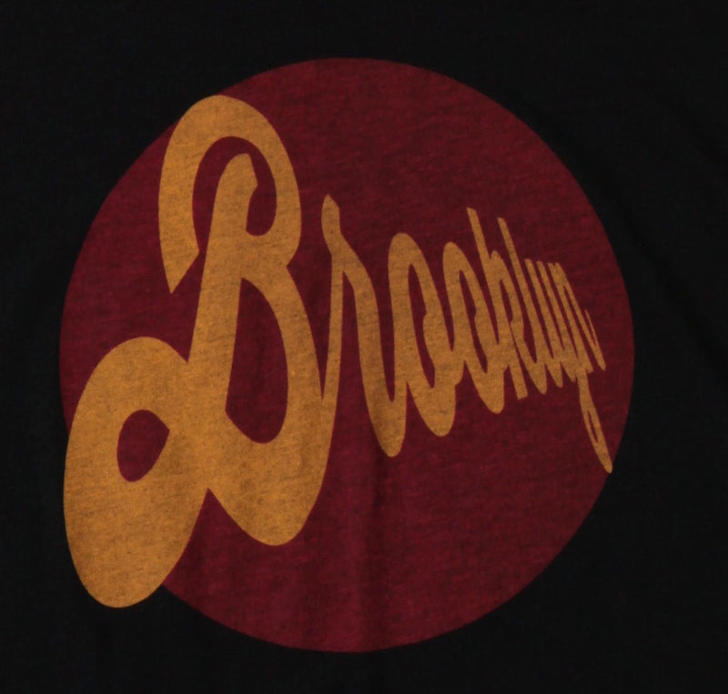 Retro style graphic forms a burgundy circle on the center chest with orange lettering.  The font is a classic script that crescendos from right to left.