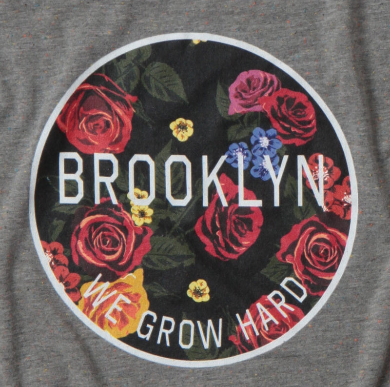 detail of the we grow hard women's t-shirt grey off shoulder shirt with circle of flowers on front with text of we grow hard, and Brooklyn intersecting it