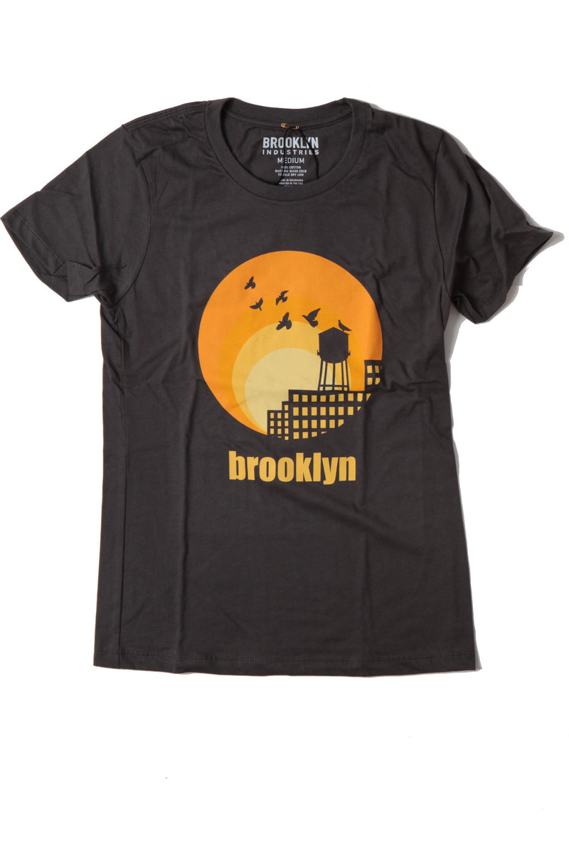 Gradiant Yellow Sun with Silhouette Of WaterTower and Birds.  Brooklyn Written in same Yellow underneath on Heavy Metal T