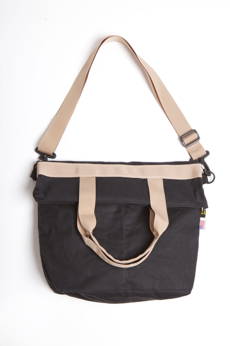 Waxed zip messenger bag in black wax with tan handles and straps.