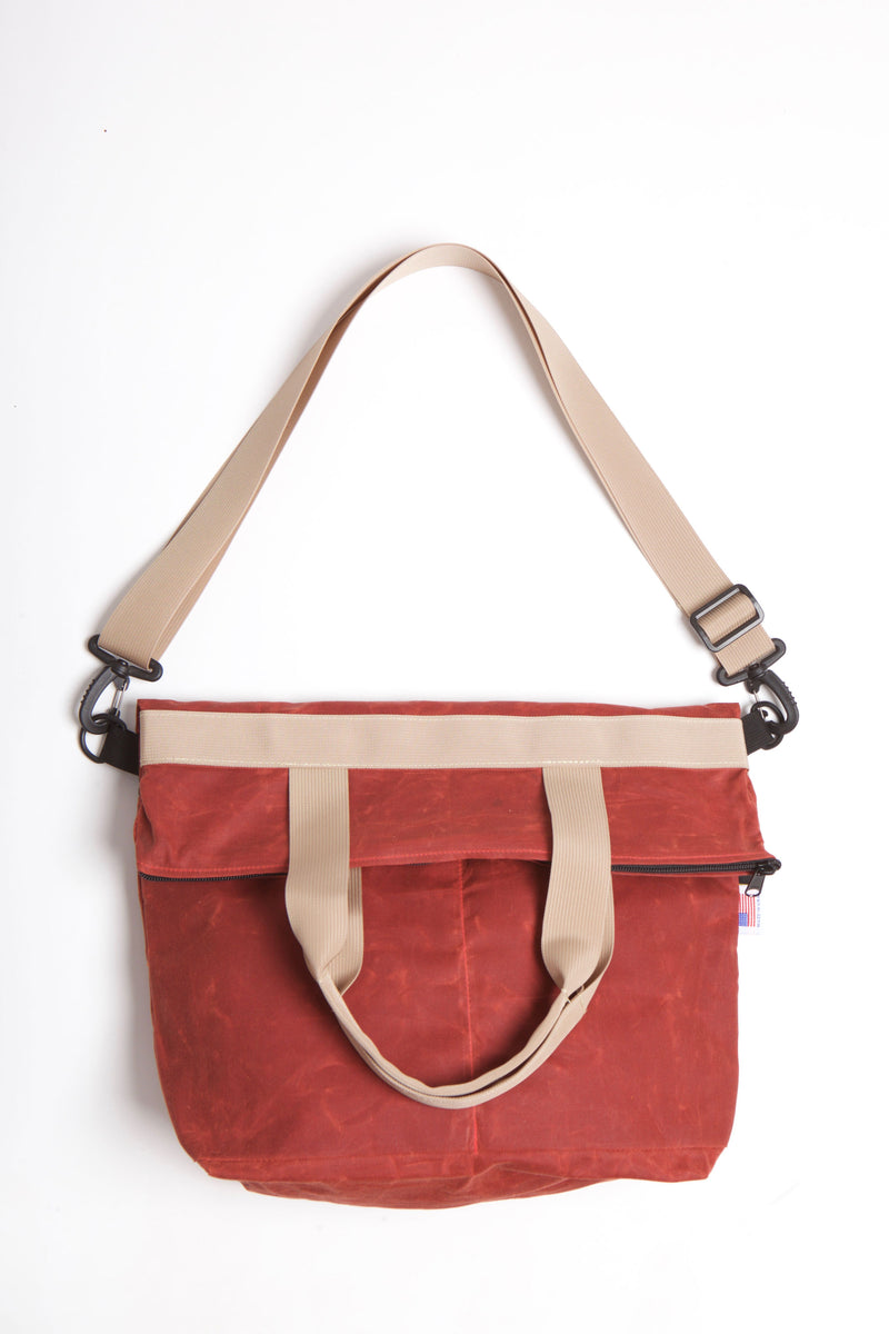 Waxed zip messenger bag in burgundy wax with tan handles and straps.