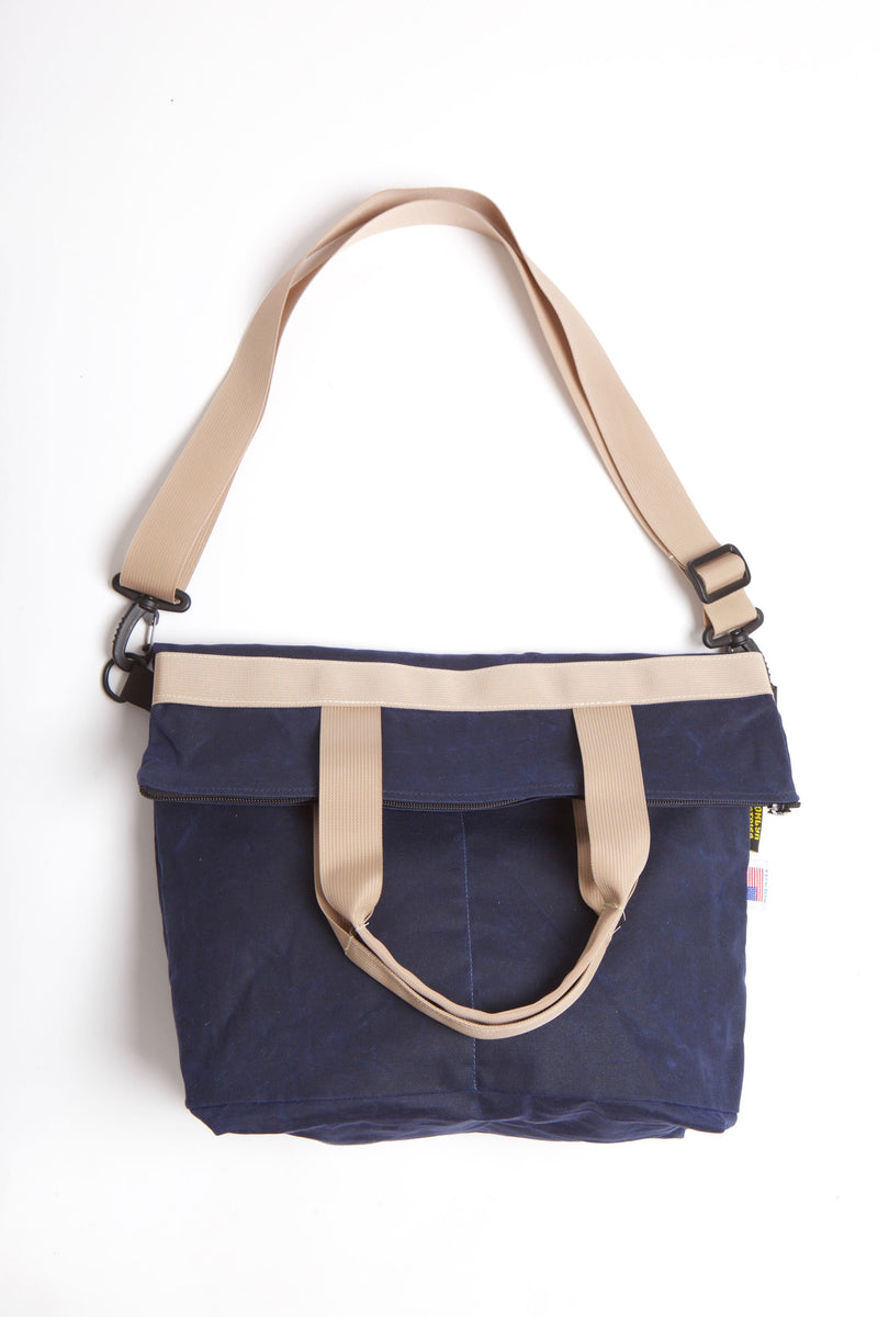 Waxed zip messenger bag in navy wax with tan handles and straps.
