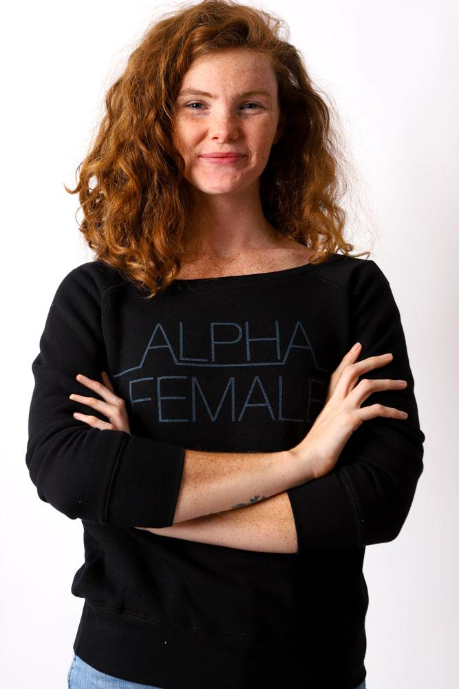 women smirks at camera with arms crossed wearing an Alpha Female black sweatshirt