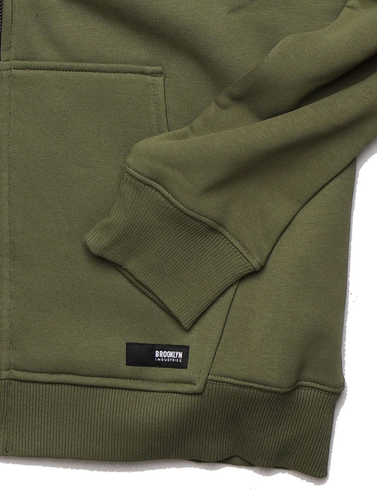 DETAIL OF THE BROOKLYN INDUSTRIES LABEL ON THE LEFT POCKET OF THE ARCHED BK APPLIQUE ZIP UP SWEATSHIRT