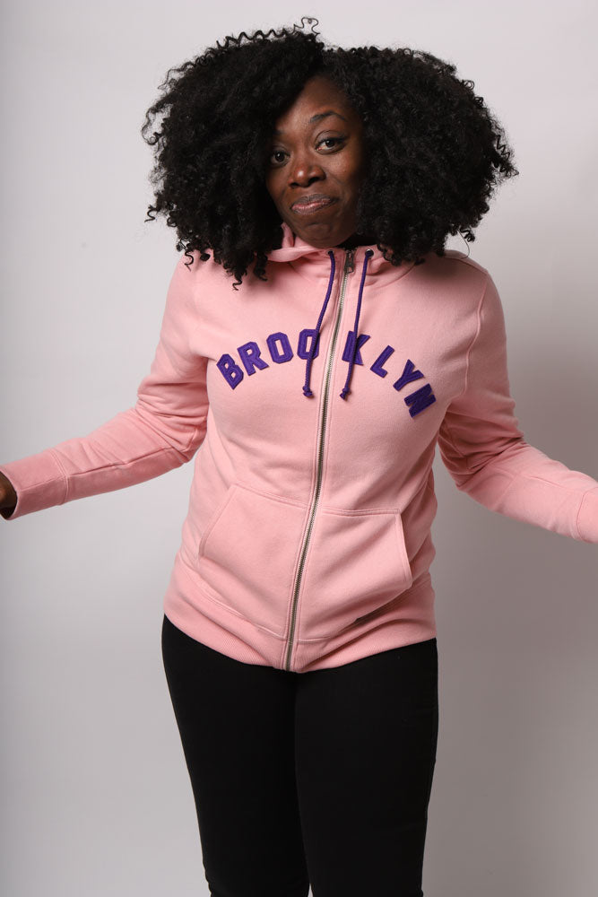 WOMEN SMIRKS AT THE CAMERA WITH ARMS OUT, WEARING THE PINK ARCHED BK APPLIQUE SWEATSHIRT WITH PURPLE LETTERING OF BROOKLYN ON THE CHEST