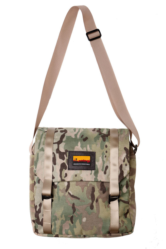 cross body style bag with a flip top and khaki webbing straps. flat lay image of the mail bag in arid camo