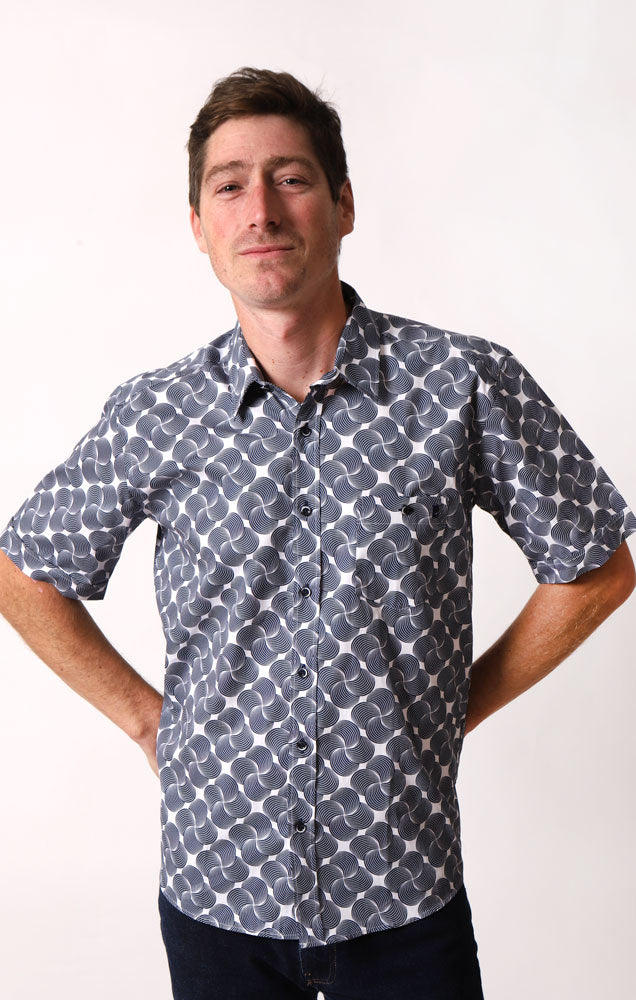 MAN SMILES AT CAMERA WITH HANDS BEHIND HIS BACK WEARING A BUTTON UP SHORT SLEEVE WOVEN SHIRT WITH A VERY GRAPHIC BLUE SWIRLING PATTERN
