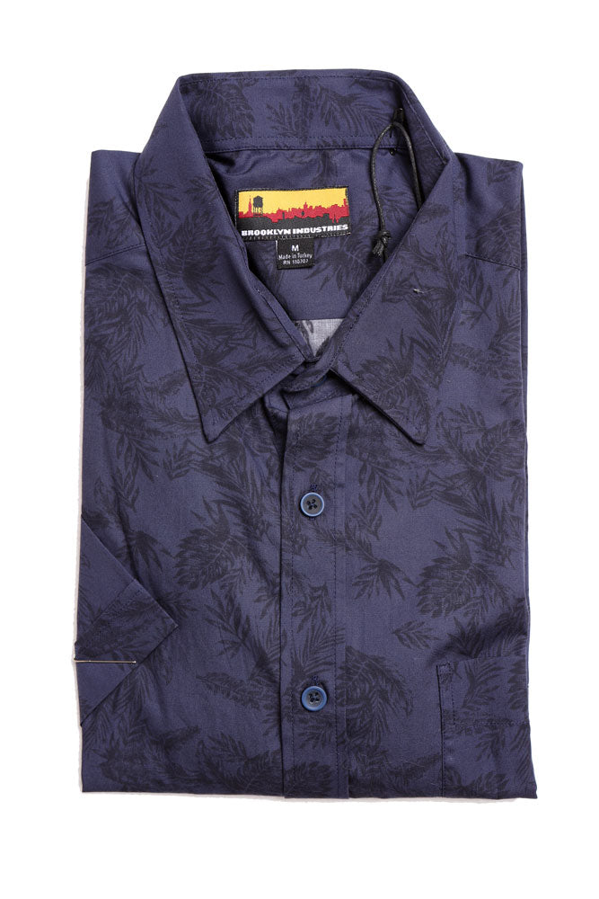 folded short sleeve woven shirt in blue with darker blue tropical leaves design
