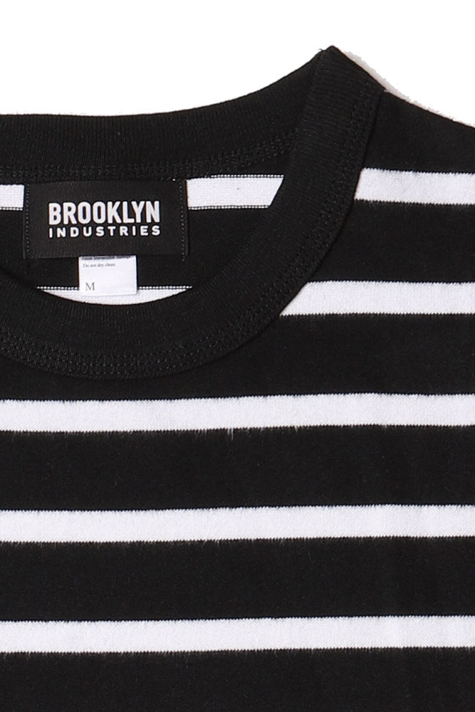 detail of knit black and white striped men's short sleeve shirt and the black and white Brooklyn Industries tag in the collar.