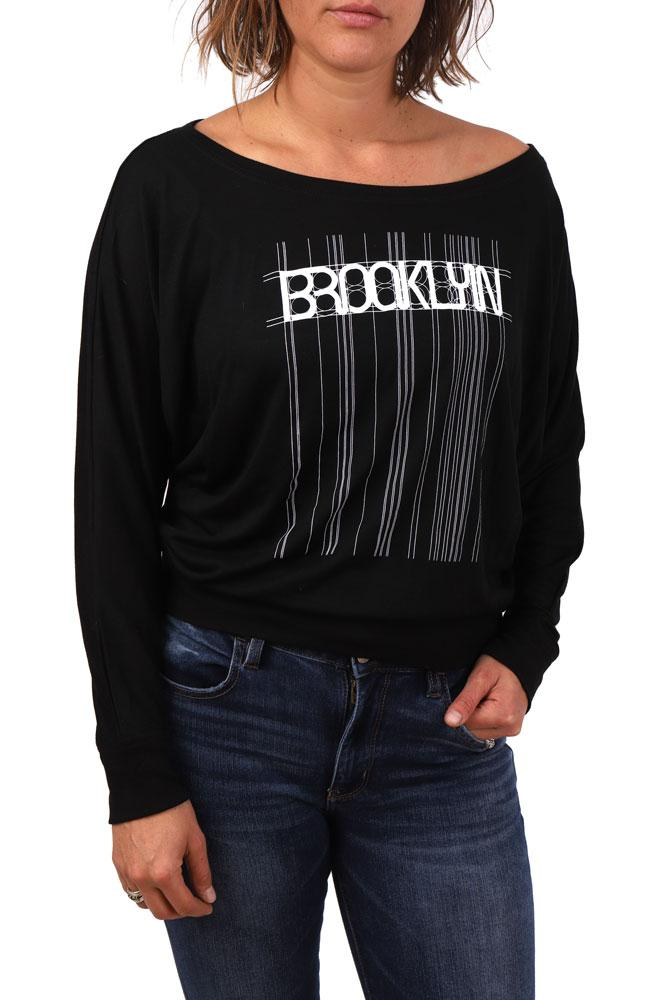 model wears black long sleeve with Brooklyn graphic in white, lines and detail extending the entire length of the shirt, with one hand in jeans pocket