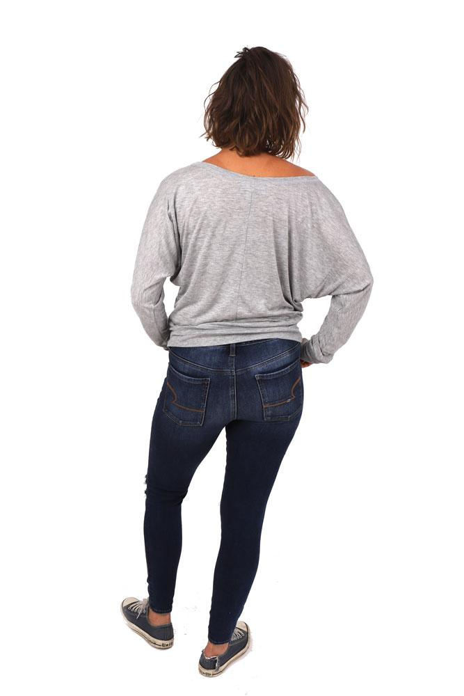 back view of model in jeans and off the shoulder grey bk trains long sleeve with seam down the center of the back