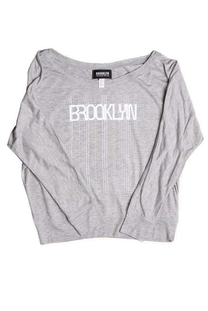 flat lay of grey long sleeve with Brooklyn graphic in white, lines and detail extending the entire length of the shirt