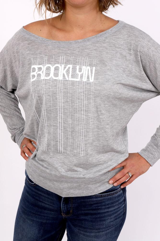studio shot of model in grey long sleeve with Brooklyn graphic in white, lines and detail extending the entire length of the shirt hands on hips