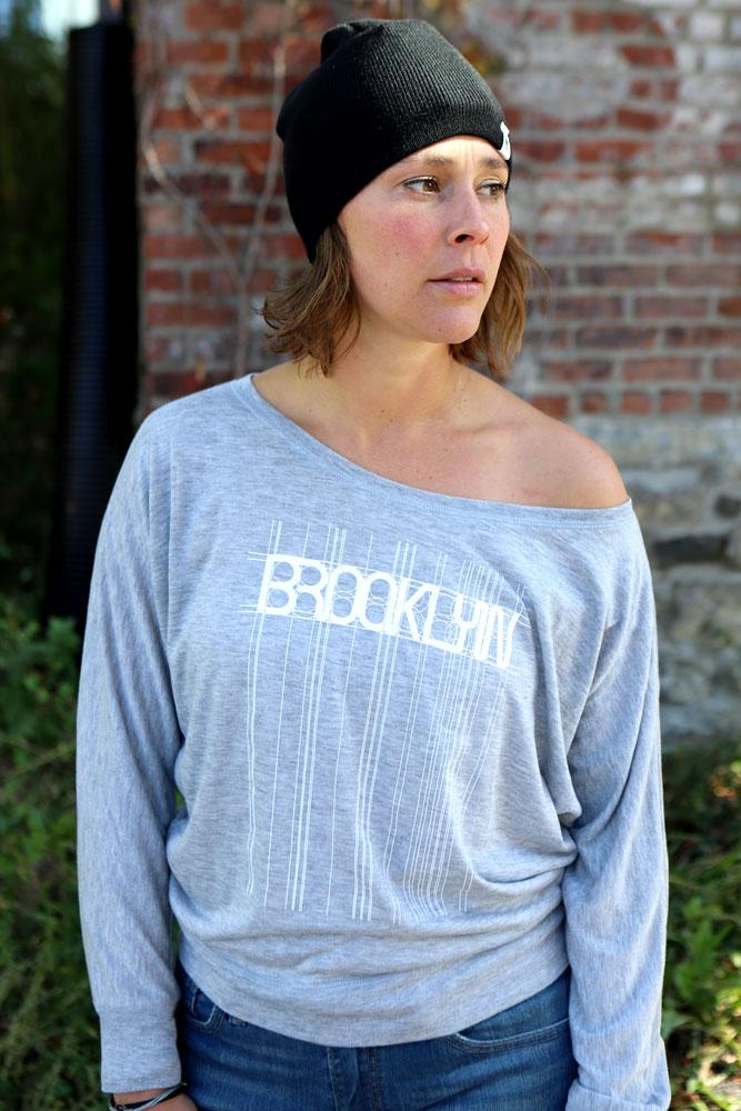 model wears grey bk trains long sleeve and black water tower beanie in a street scene