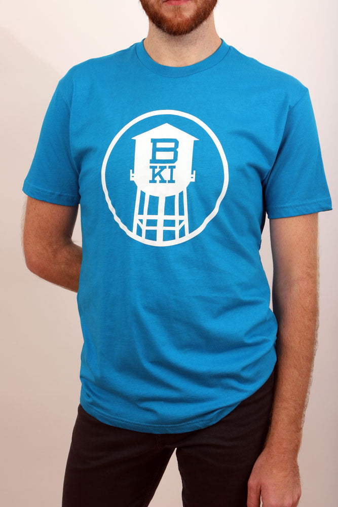 close up of the bright blue BKI HIGH TOWER tshirt, white circle houses water tower silhouette with BKI cut out of the body