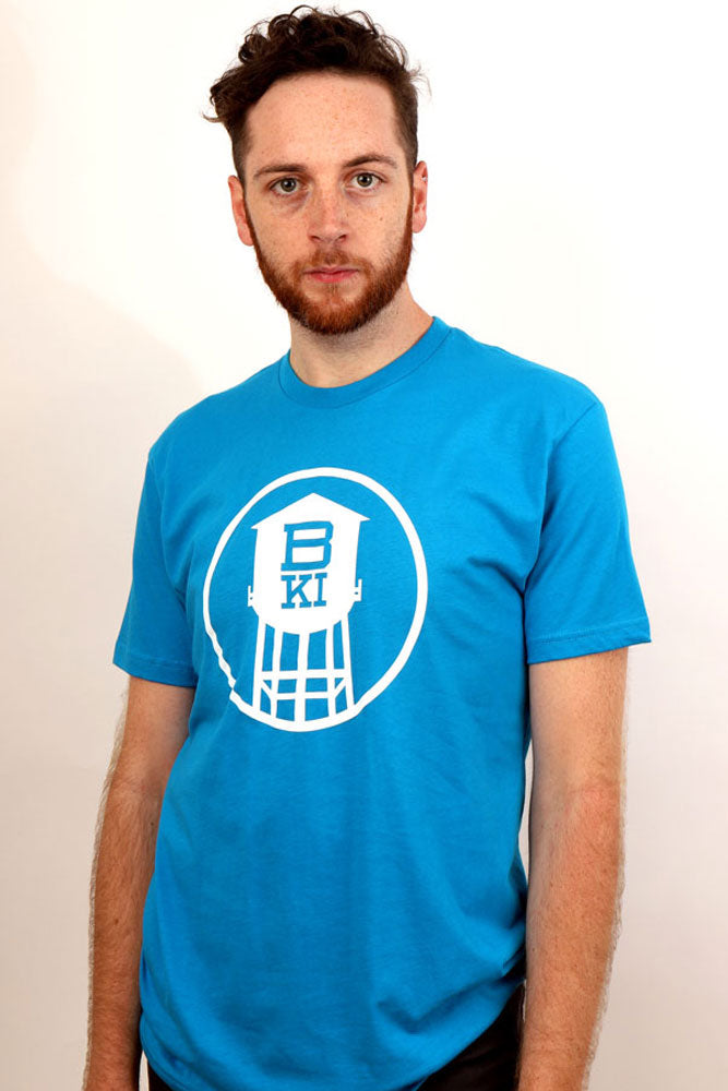 man looks straight into the camera, wearing a bright blue tshirt with a white water tower in a circle. BKI is cut out of the tower body.