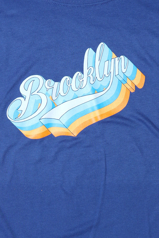 DETAIL OF THE BK PLATFORM SCRIPT GRAPHIC ON THE BLUE T-SHIRT