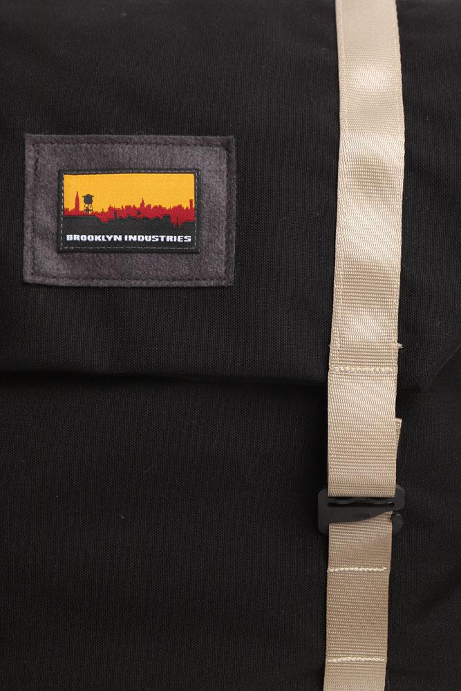 detail of Brooklyn Industries patch on the front flap of the black mail bag, with khaki strapping and hook for closure.