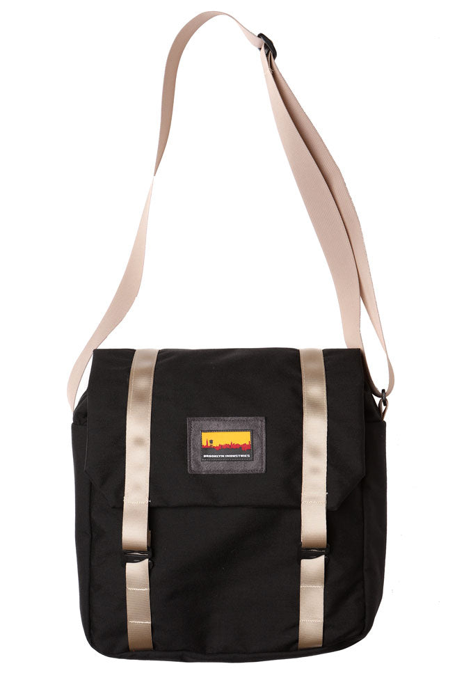 cross body style bag with a flip top and khaki webbing straps. flat lay image of the mail bag in black