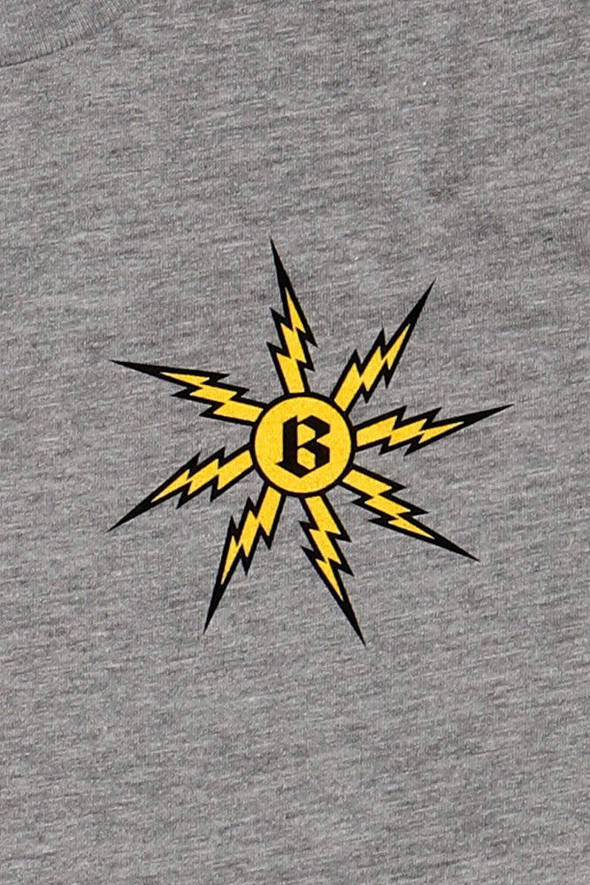 detail of flat lay grey t-shirt with yellow lightening bolts in a circle, striking the letter b, on the left chest