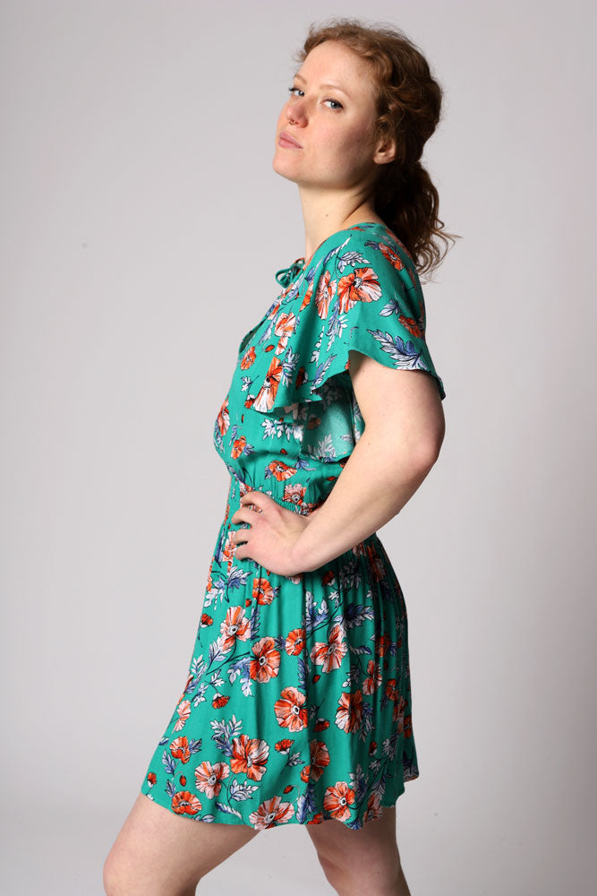 Be always blooming in this floral printed rayon crepe dress with a smocked waist, flutter sleeves, and a tie neckline detail.