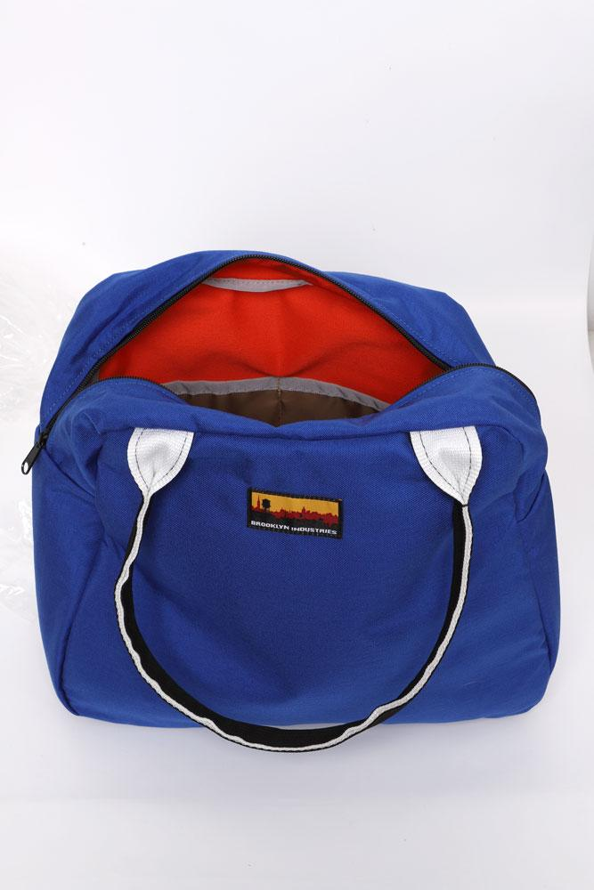 MEDIUM BOWLING BAG OPEN TO SHOW LINING COLOR. BLUE WITH ORANGE LINER
