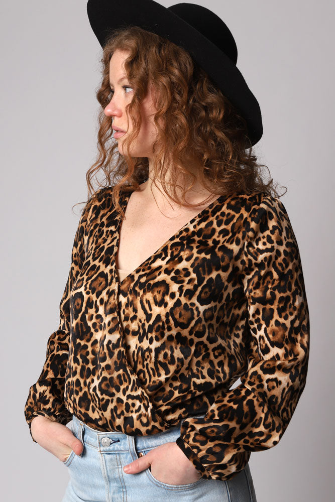 leopard print satin bodysuit with a wrap front v-neckline and long sleeves. Leopard print ton with black on the under body snap area.