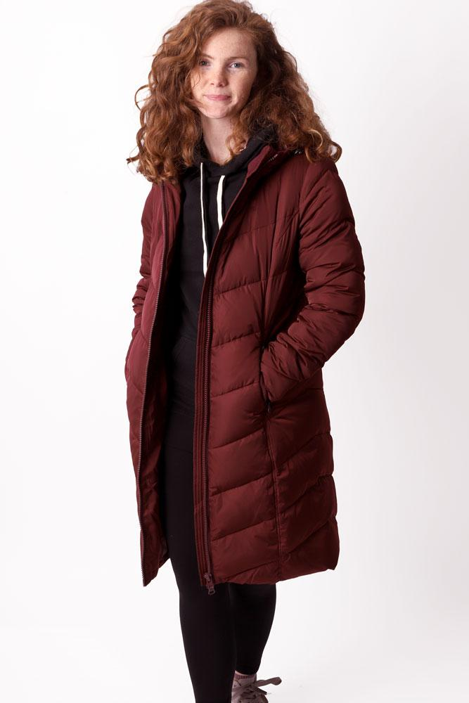 Women with curly red hair wears long Fjord coat in burgundy