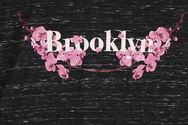 detail of flat lay black  blended long sleeve with white Brooklyn text and pink floral design on chest