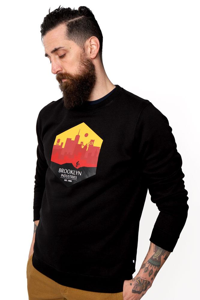 man looks down to the side, wearing a black sweatshirt with our City Ride red and yellow graphic on the chest.
