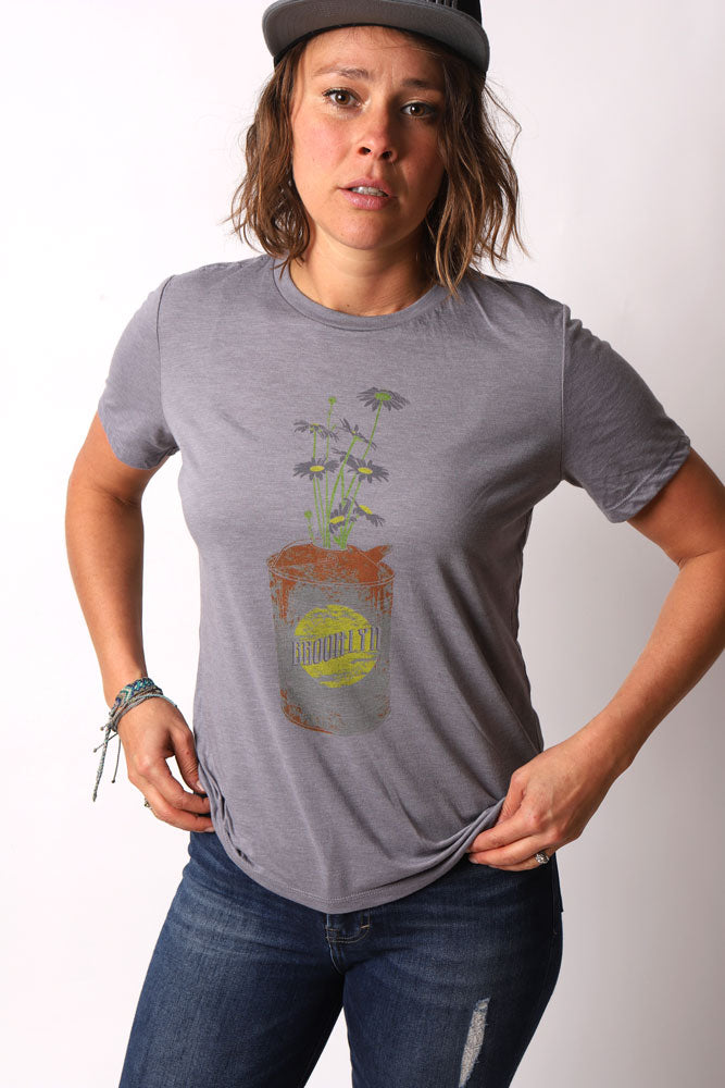 FEMALE MODEL IN FLAT BRIM CAP PUTTING HER HANDS IN HER POCKETS, WEARING THE GREW DAISY CAN T-SHIRT