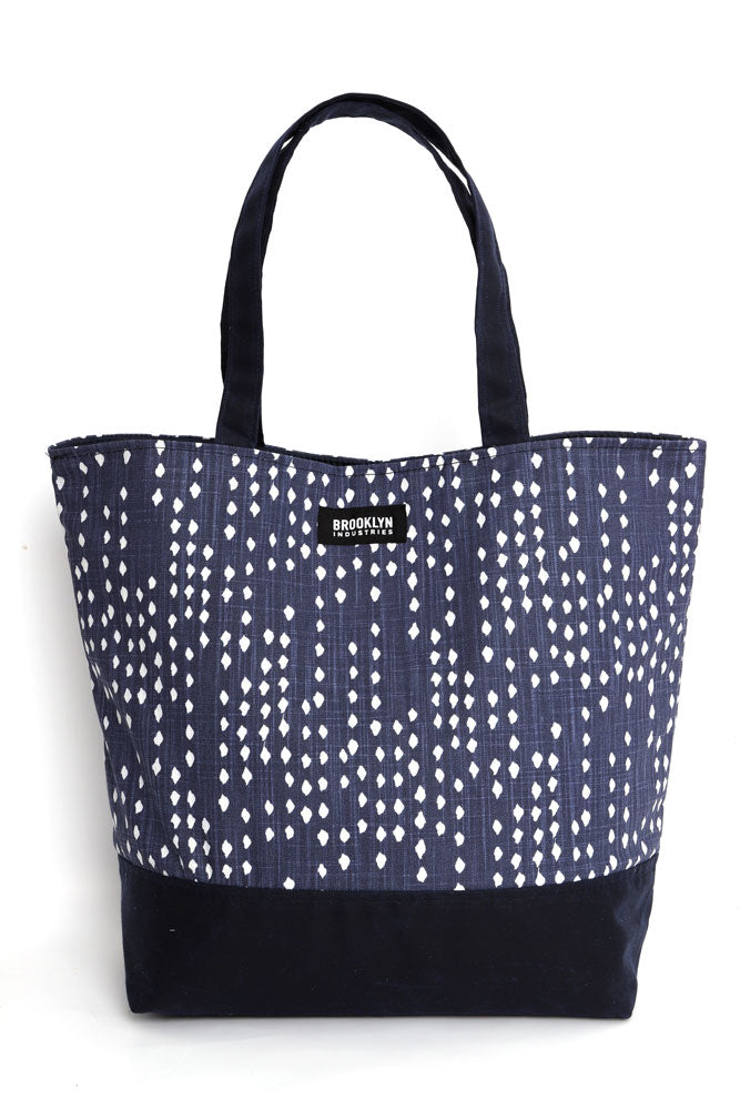 Canvas tote in blue denim with white polka dots, and navy waxed canvas base and handles, front view