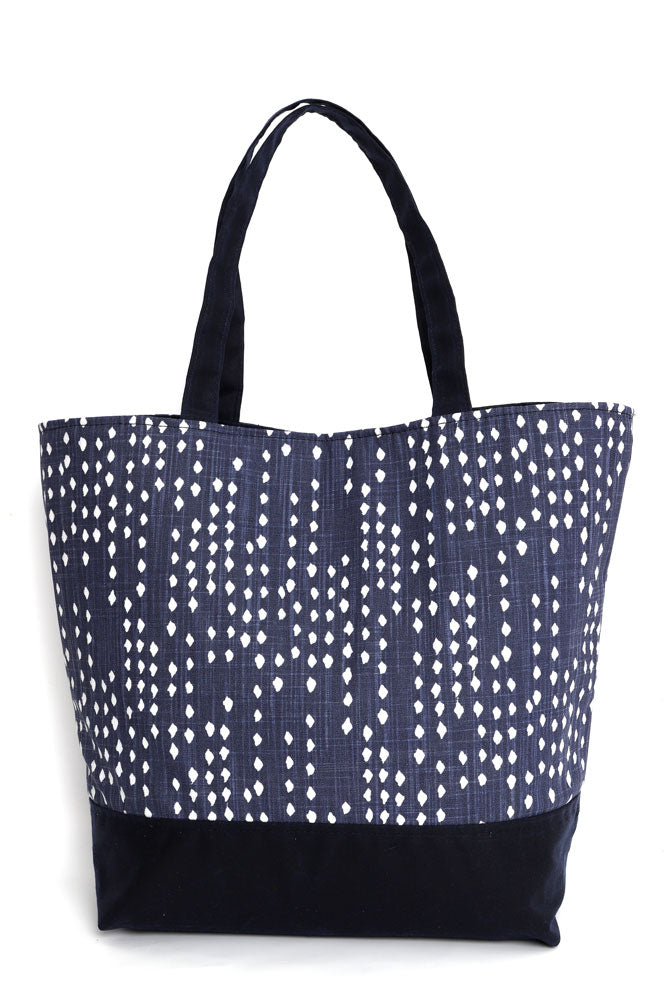 Canvas tote in blue denim with white polka dots, and navy waxed canvas base and handles,  back view