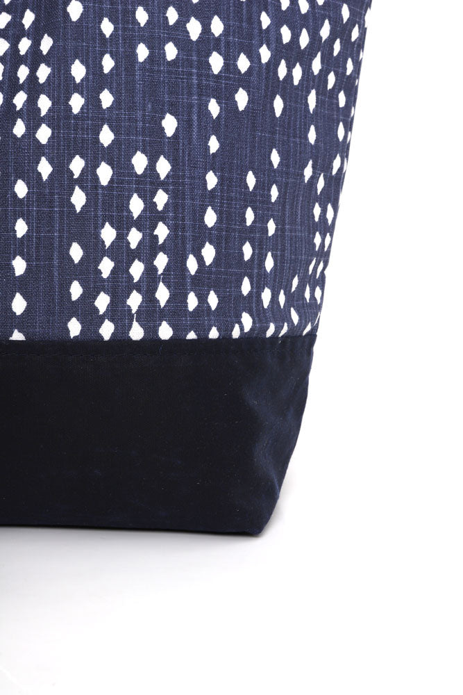 detail of Canvas tote in blue denim with white polka dots, and navy waxed canvas base and handles,