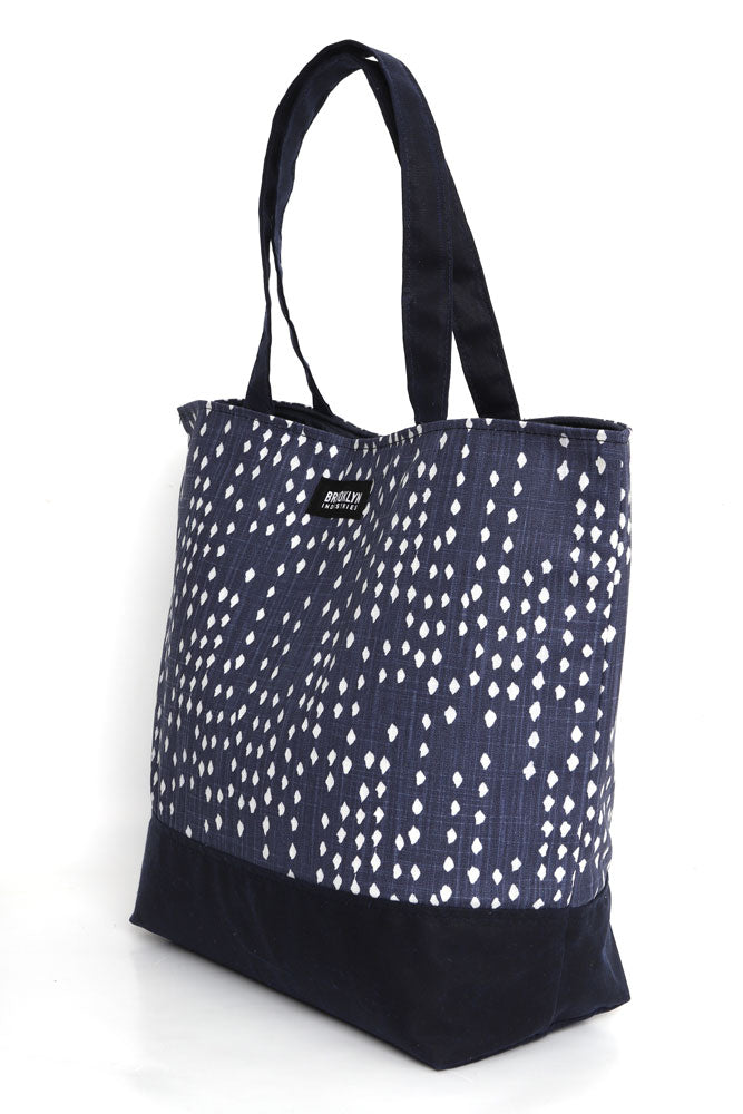 Canvas tote in blue denim with white polka dots, and navy waxed canvas base and handles,  side view