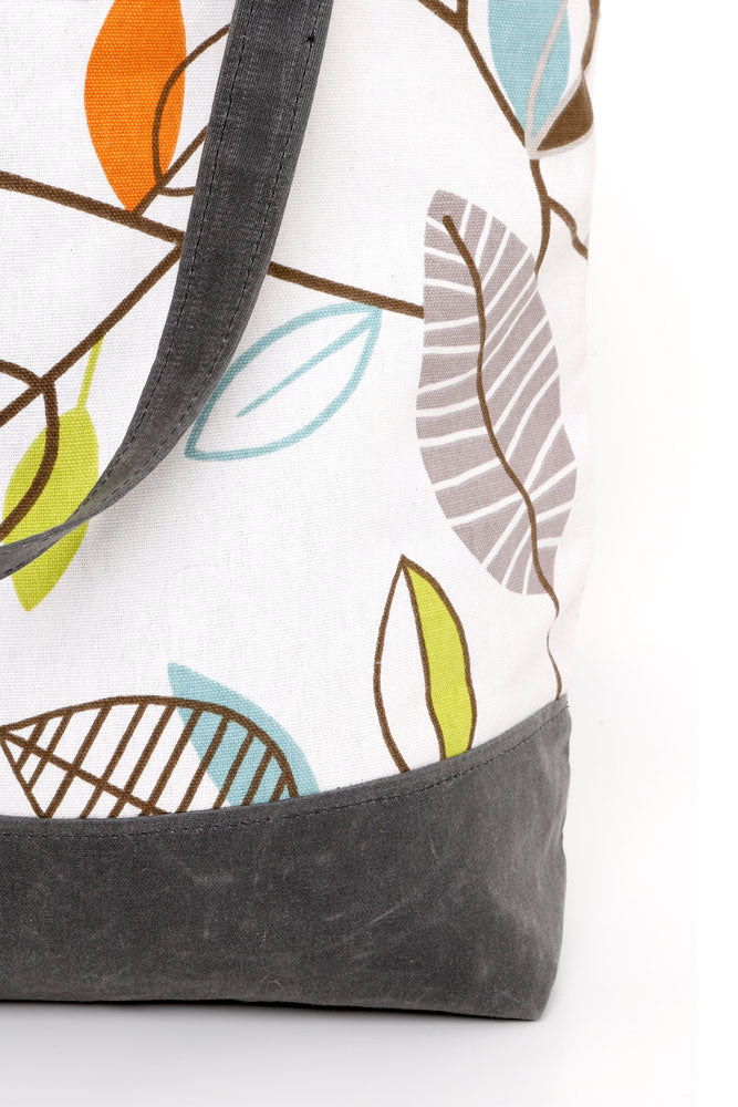 DETAIL OF CANVAS TOTE BAG WITH LEAF DESIGN TOP PANEL AND WAXED CANVAS IN RHINO BOTTOM AND STRAPS