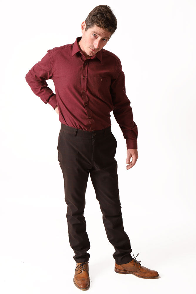 man with hand behind back wears brown pant with burgundy detail, burgundy shirt, and light brown shoes