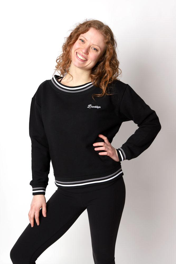 WOmen in black yoga pants and black Brooklyn embroidery sweatshirt