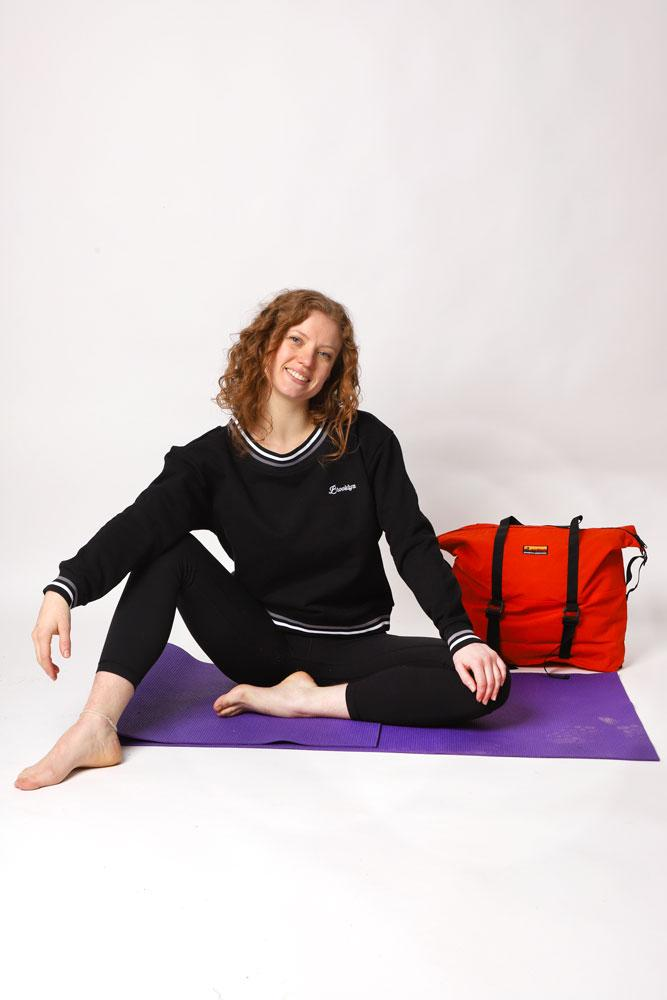 Women sits on yoga mat with BKI Yoga Bag, wearing black BROOKLYN Embroidery sweatshirt