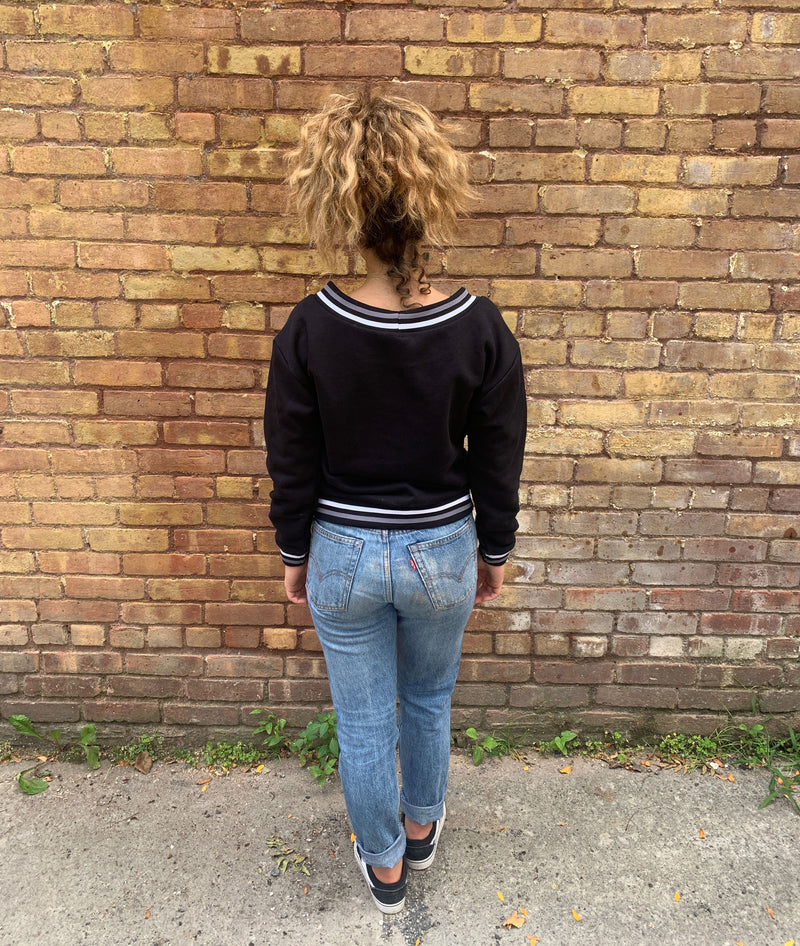 BACK VIEW OF MODEL IN BLACK EMBROIDERY SWEATSHIRT IN FRONT OF A BRICK WALL