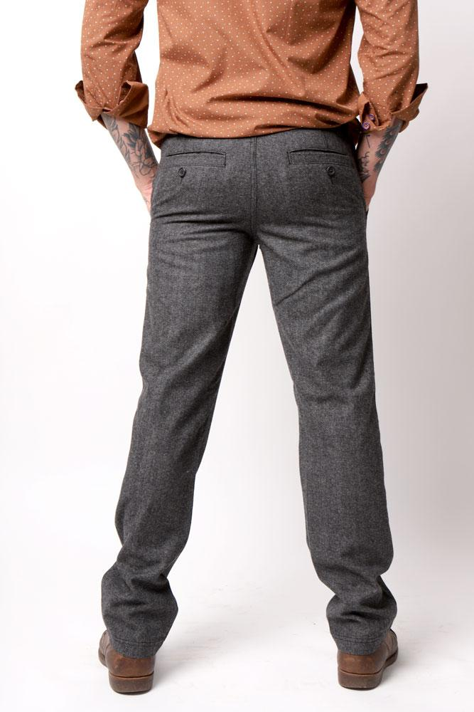 man with arm tattoos wears charcoal wool pant and brown dress back front view