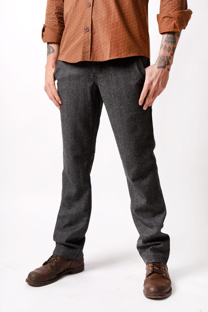 man with arm tattoos wears charcoal wool pant and brown dress shirt front view