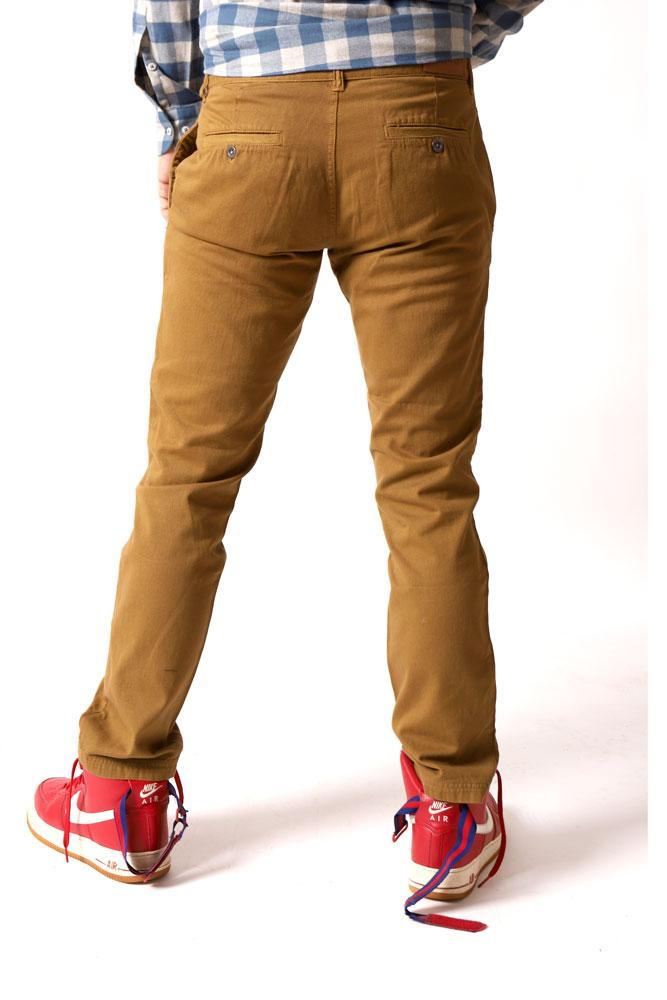 BACK VIEW OF MALE MODEL IN TOAST COLORED FADED PANTS