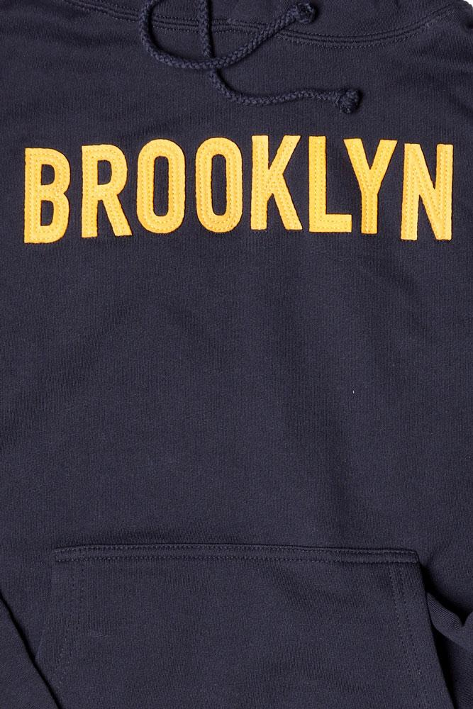 DETAIL OF NAVY HOODED SWEATSHIRT WITH YELLOW APPLIQUE LETTERING BROOKLYN ON CHEST