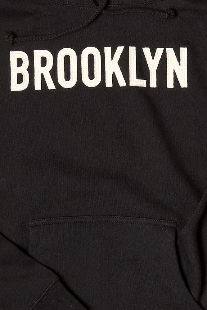DETAIL OF BLACK HOODED SWEATSHIRT WITH WHITE APPLIQUE LETTERING BROOKLYN ON CHEST