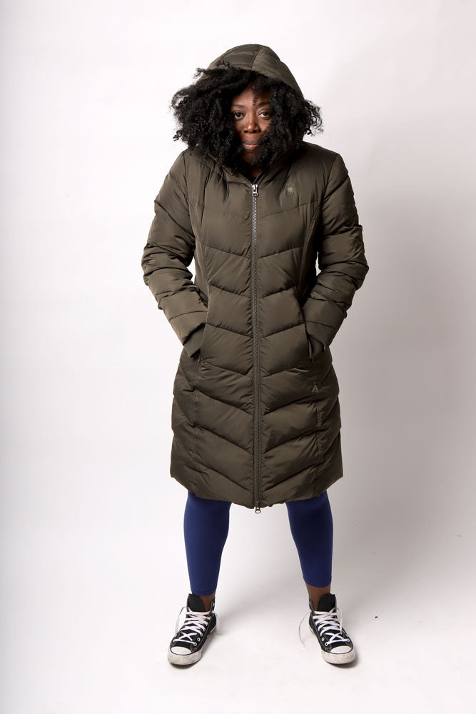 front view  of women with afro stuffed into the hood of the olive colored below the knee length puff coat