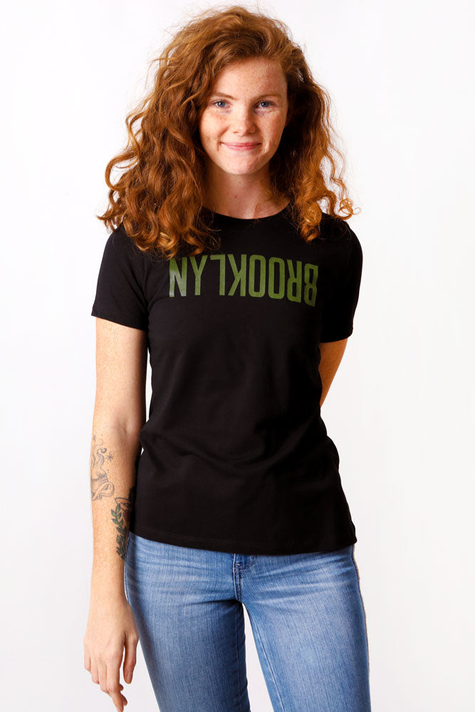 women smiles at camera in black tshirt with Brooklyn text flipped upside down across the chest in olive green